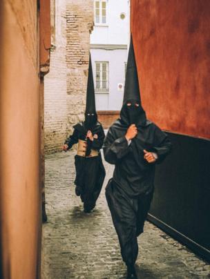 Dos feligreses llegando tarde a una procesión en Sevilla
