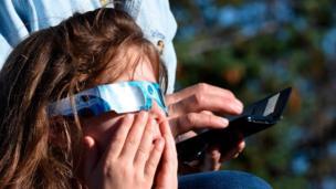 Una niña observa el eclipse con unos protectores solares puestos