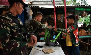 Two members of the security forces in Davao city examine a man's bag at a checkpoint on a road into the city