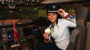 Sam Quek in the cockpit of a plane with a pilot's hat on, holding her medal