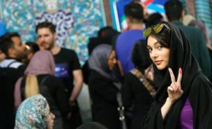 An Iranian woman (R) flashes the victory sign as she waits with others to cast her ballot in the Iranian presidential elections at a polling station in Tehran, Iran, 19 May 2017