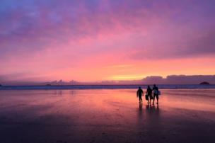 Tres personas caminan en la playa al atardecer
