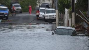 A car is viewed stuck in a flooded street in the San Juan neighbourhood of Santurce.