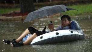 A man sits on an inflatable boat in flood waters in Houston.