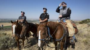 The Madison County Sheriff's Mounted Patrol watch the eclipse atop horses on Menan Butte on August 21, 2017 in Menan, Idaho.