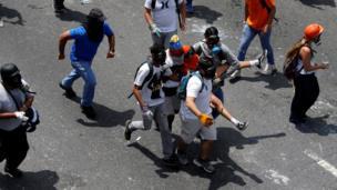 Jóvenes cargan a un herido