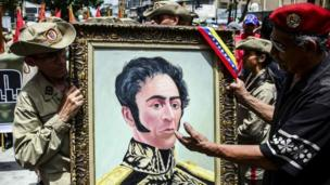 Venezuelan militias hold a portrait depicting Venezuelan Liberator Simon Bolivar as they demonstrate their support to the government of Venezuelan President Nicolas Maduro and against US President Donald Trump, in Caracas, on August 14, 2017.