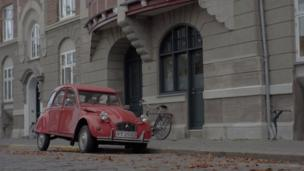 A old fashioned red car stands out from a grey Danish street
