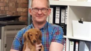 Tomasz holds Ralphy the dog on his lap in the office