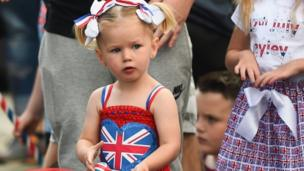 A child is pictured in a union jack dress with ribbons in her hair
