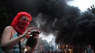A demonstrator reviews a photo on her phone while a fire burns in the middle of town