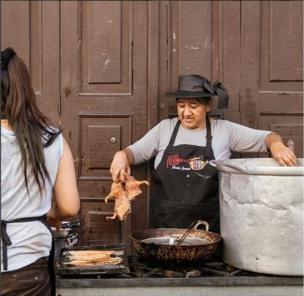 Mujer prepara un cuy y lo saca de una olla