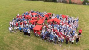 Tom Barton a year 6 teacher at Broadmeadow Junior School in Kings Norton, Birmingham UK, designed the Union Jack flag on the field and then had the children come in to school wearing either red, white or blue to create the flag. Credit: Tom Barton