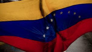 A shadow of a person seen through a Venezuela flag