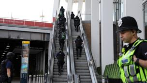 Armed police climb escalator in The Shard