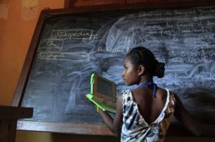طفلة تحمل حاسب لوحي وتكتب على سبورة