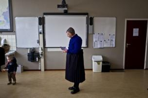 An elderly woman waits her turn to receive her ballot prior to casting her vote for Dutch general elections at a polling station set up in a school in Staphorst, Netherlands, 15 March