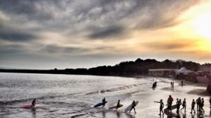 Young lifeguards carry out sea training exercises as the sun goes down over Barry Island