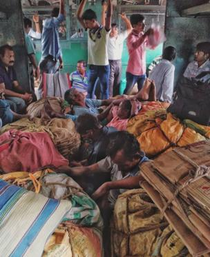 Passengers crowd the inside of a luggage compartment in a local train in Kolkata.
