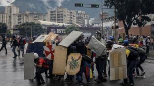 متظاهرون يحملون دروع