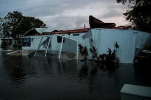 Flood water from Hurricane Irma surround a damaged mobile home in Bonita Springs, Florida, 10 September