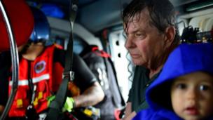A man is pictured with a small child on board a rescue helicopter