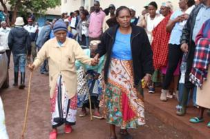 Elderly woman wey dem assist to come vote inside di polling station for Mutomo primary school in Gatundu, during di presidential electionre-run.