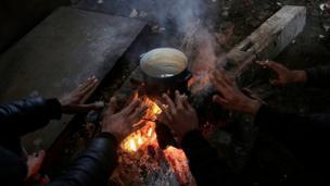 En basit insani ihtiyaçlarını karşılamakta zorlanan mülteciler yaktıkları ateşle ısınmaya çalışıyorlar.