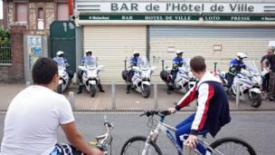 Police motorcyclists wait on pavement