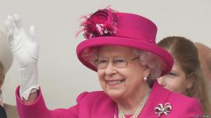 The Queen waving while watching the carnival