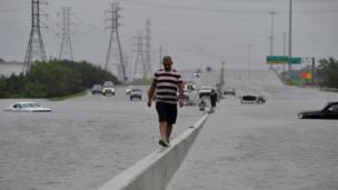 A stranded motorist escapes floodwaters on Interstate 225 after Hurricane Harvey inundated the Texas Gulf coast (27 August 2017)