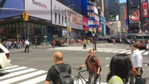 A red car is wedged against a lamp post after crashing in New York's Times Square