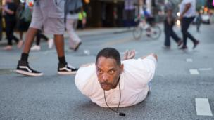 A man lays on the ground after yelling 'Don't shoot me' at police during a rally in Dallas, Texas - 7 July 2016