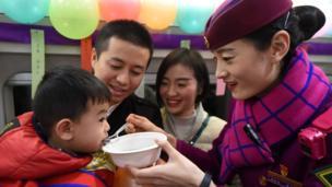 中国高铁的乘务员在一列列车上为旅客送上汤圆,欢度佳节