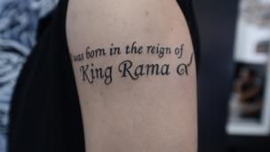 "Tattoo reads in English: ""I was born in the reign of King Rama"" with the Thai number 9"
