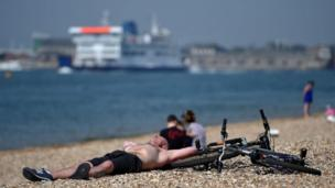 Man lying on Southsea beach beside bike.