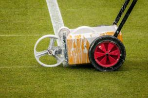 A machine that paints white lines on grass