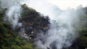Smoke rises from the wreckage of a passenger plane in the Margalla Hills, north of Islamabad