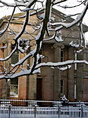 snow tree against stone building