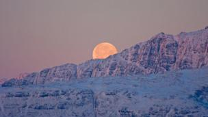moon rising above mountains