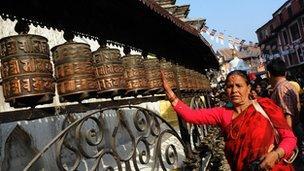 Woman spinning a prayer wheel