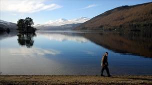 Man walking by a loch