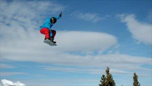 A snowboarder performs a jump.