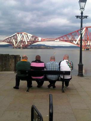Men sitting on a bench looking towards the Forth Rail Bridge