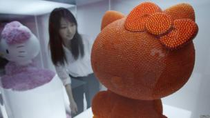 A woman looks at an artwork based on Hello Kitty in Tokyo