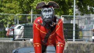Life-size gorilla sculptures on top of a boat in Bristol.