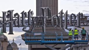 Builders put up the Harry Potter sign at Nelson's Column in London