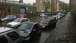 Firefighters and parked cars in flood on Balcarres Street in Edinburgh