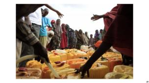 Somali refugees wait to fill cans with water