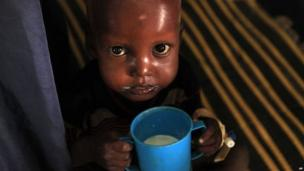 Starving children like this little boy are fed milk drinks to help them get stronger.
